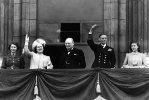 The British Royal Family and Prime Minister Churchill wave joyously to the crowds gathered outside Buckingham Palace on V.E. Day marking the end of World War II in Europe. From left: Princess Elizabeth, Queen Elizabeth, PM Churchill, King George VI, and Princess Margaret.